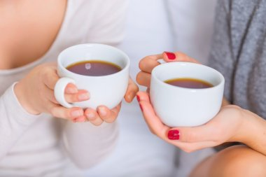 Two young ladies holding teacups.