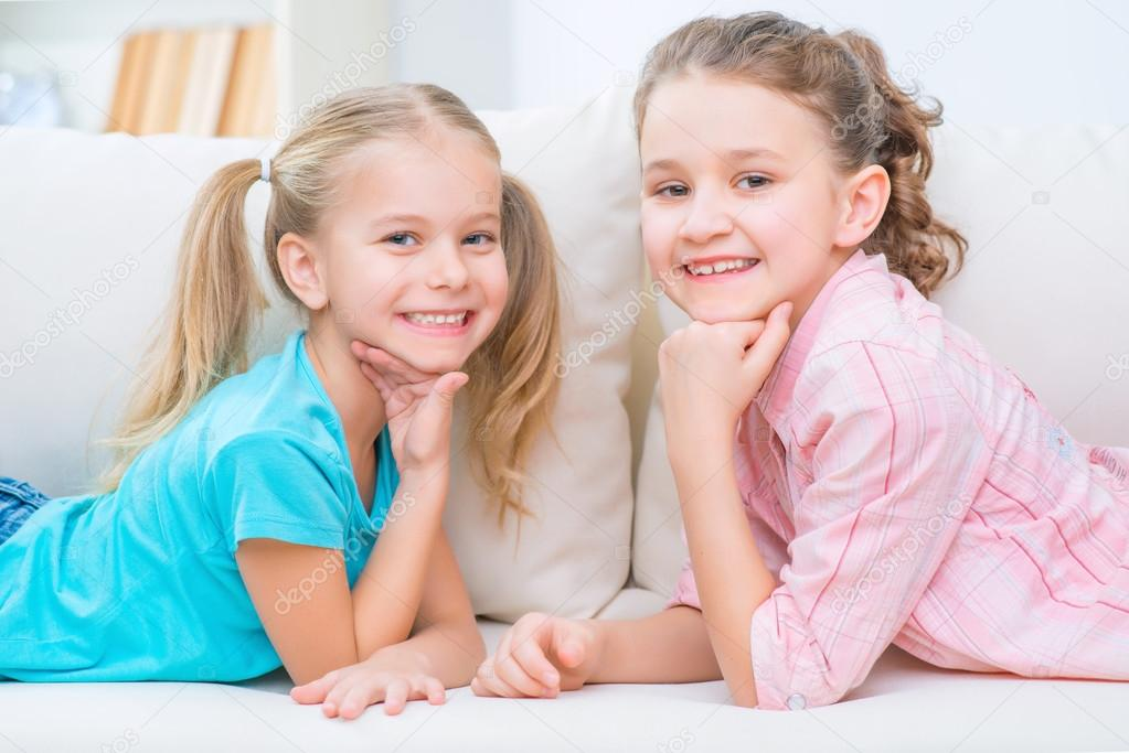 Cheerful Little Sisters Sitting On The Sofa Stock Photo Image By C Dmyrto Z 95159674