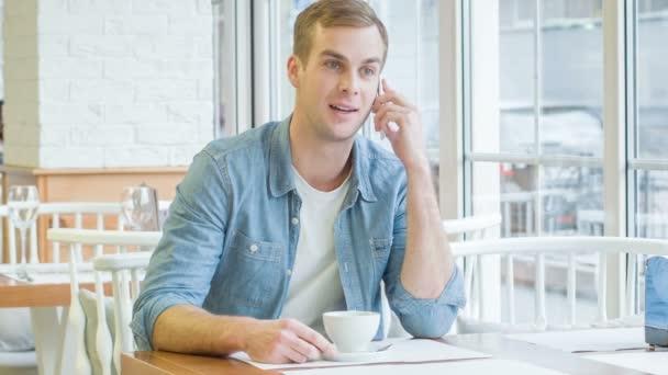 Mladý pohledný muž má telefonní hovor.