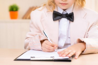 Little business girl is filling out a paper.