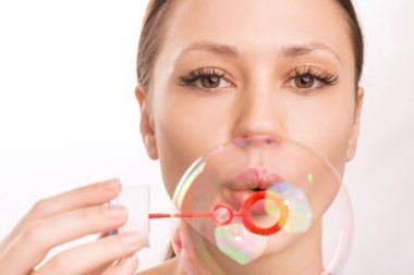 Young girl blowing out a soup bubble.