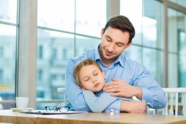 man holding his sleeping daughter