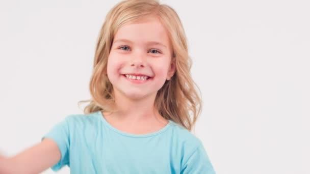 lachendes Mädchen winkt jemandem zu.