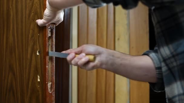 Nahaufnahme. Tischler mit der Raspel bereitet das Loch für das Schloss einer Holztür vor. Bauwirtschaft. Verfilmung.