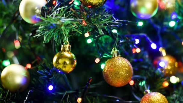 Veselé Vánoce a šťastný nový rok. Detailní záběr blikajících světel a míčků na vánoční stromeček. Zdravím video na pozadí.