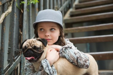 Little girl playing with her pug dog outdoors in rural areas