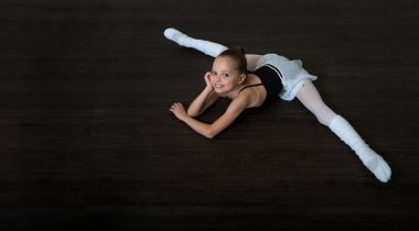 A little adorable young ballerina doing stretching exercises on