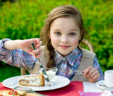 cute little girl sitting by dinner table and eating
