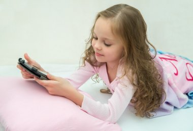 happy little girl lying on bed with tablet computer