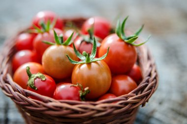 Cherry tomatoes in a small basket on an old wooden surface