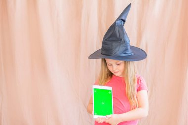 Portrait of a girl in a witch hat with a green mockup tablet screen halloween copy space