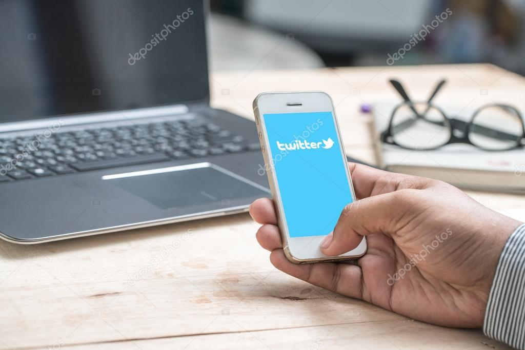 hand with smartphone and Twitter symbol on screen