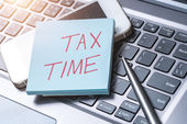tax time note on laptop keyboard