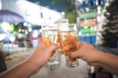 Male hands clanging beer glasses