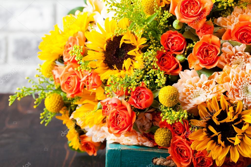 Colorful bouquet of flowers in turquoise box wooden table