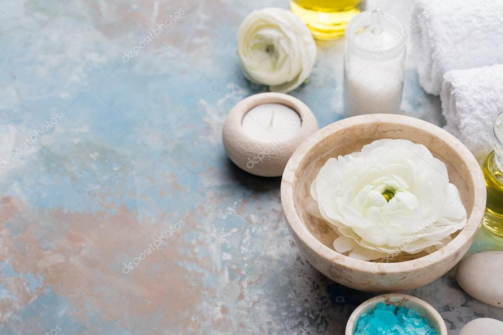 Spa and wellness massage setting, white floating ranunculus flowers