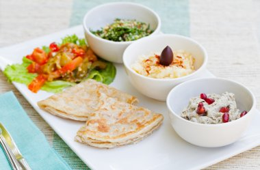 Assortment of dips: hummus, chickpea dip, tabbouleh salad, baba ganoush and flat bread, pita on a plate