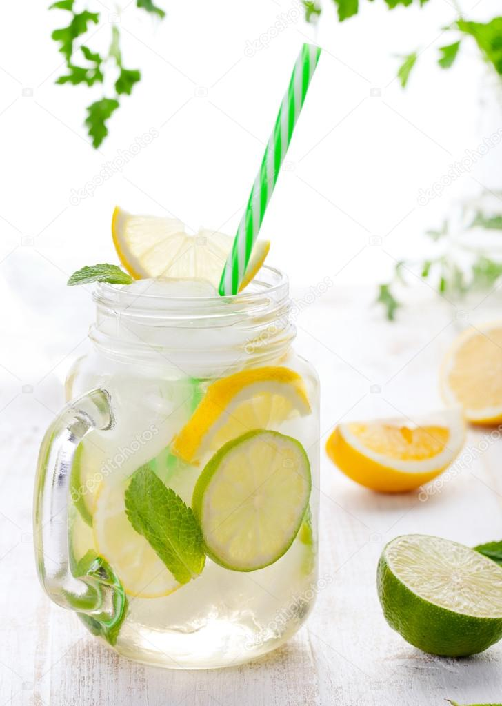 Lemonade with ice, lemon and lime slices in jar, straw.