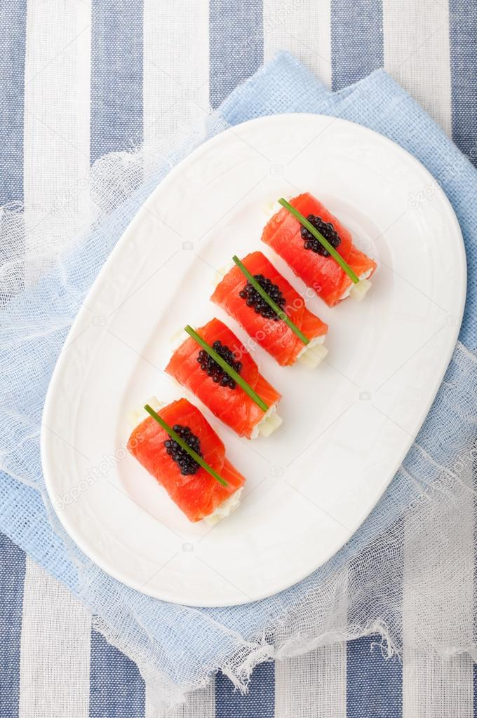 Smoked salmon rolls with cream cheese, black caviar