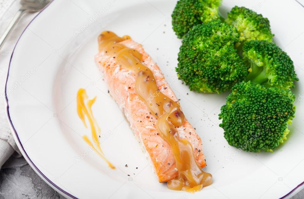 Salmon steak with creamy sauce and broccoli on a white plate