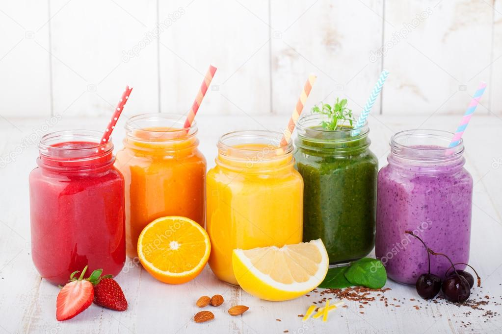 Smoothies, juices, beverages, drinks variety with fresh fruits and berries on a white wooden background.