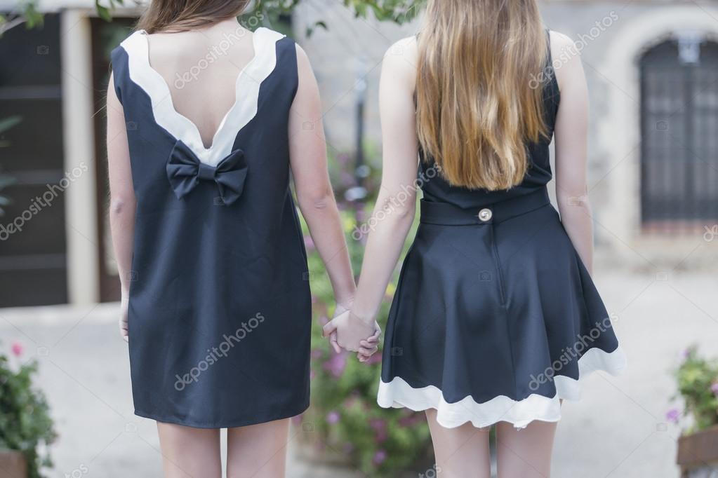 1135e63060d8 Πίσω όψη των δύο νεαρών γυναικών σε κομψό μαύρο και άσπρο φορέματα — Εικόνα  από ...