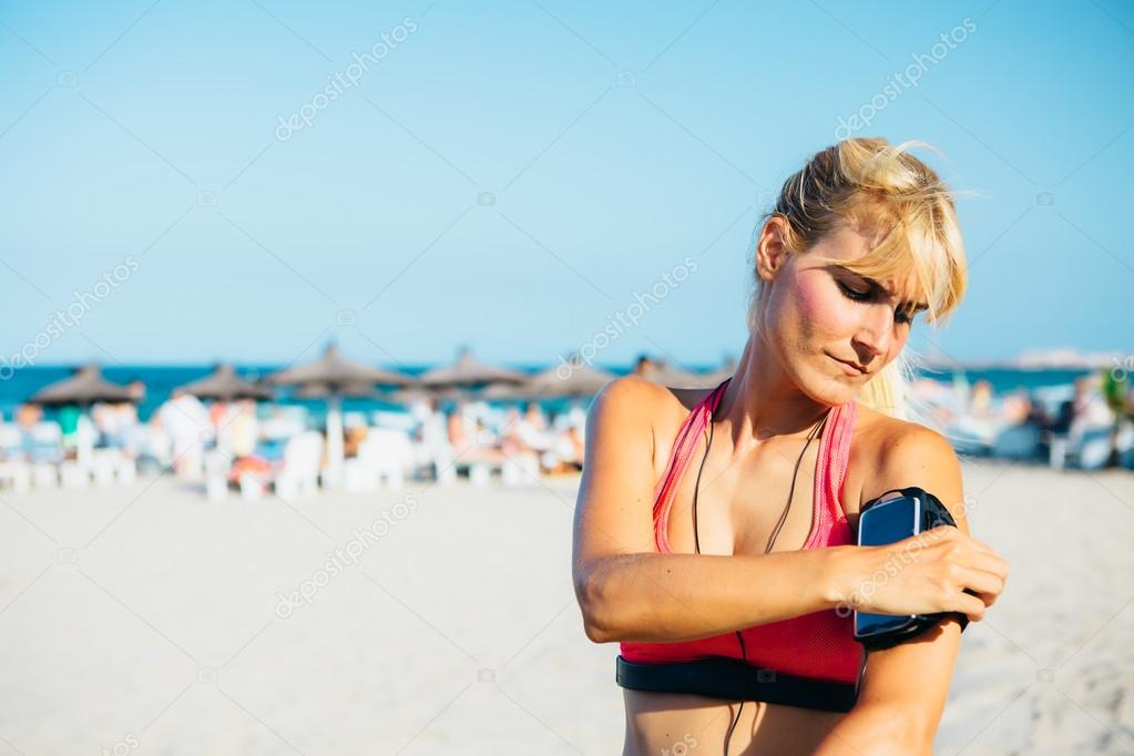 Serious athlete putting armband for phone