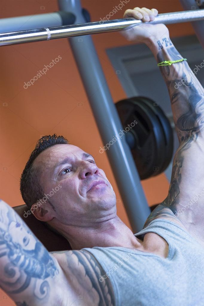 young man making military press - workout routine — Stock Photo