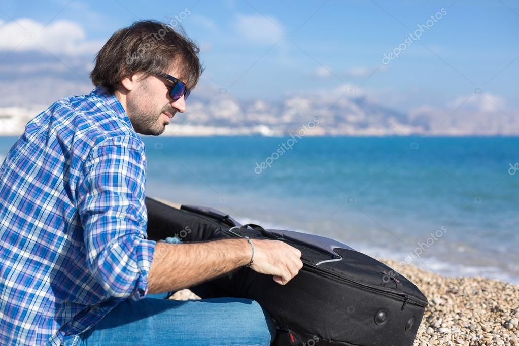 Bearded man in sunglasses zipping guitar
