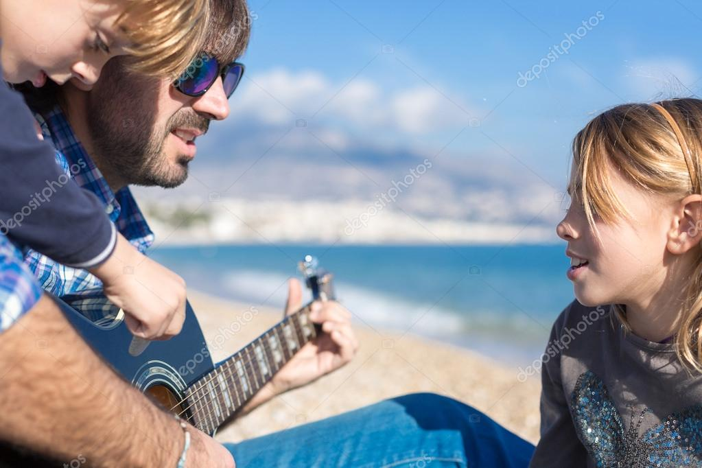Close-up of two children and father singing song on beach