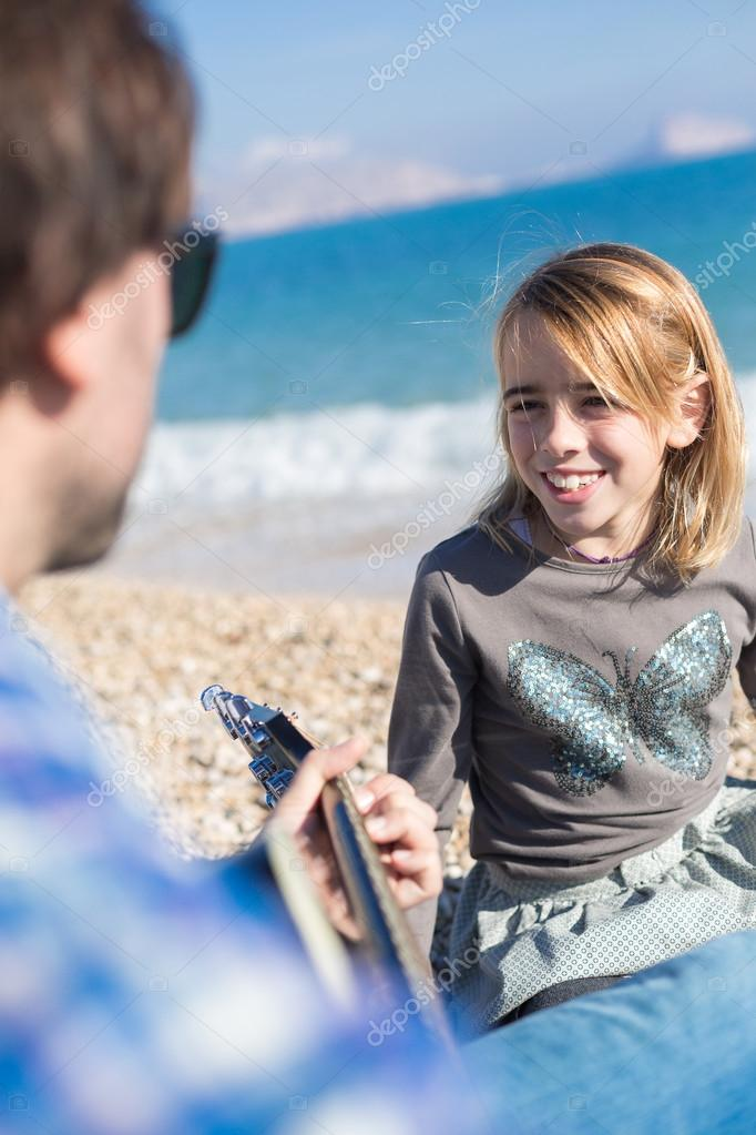 Portrait of little girl singing song on beach