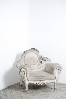 Beautiful antic armchair from solid wood in white interiour
