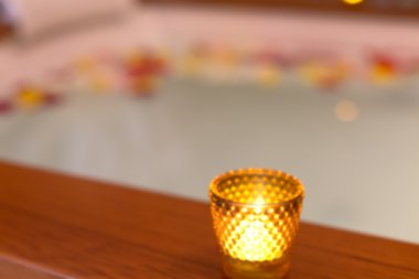 Candle in a glass candle holder near jacuzzi. Abstract blur back