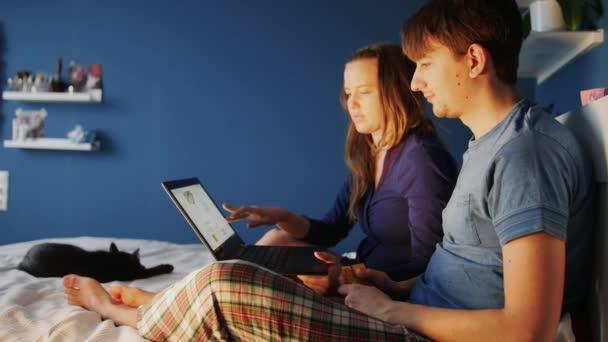 Atraktivní mladý pár s počítačem, nákupy s kreditní kartou na internetu doma