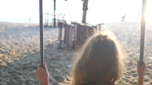 Young beautiful woman on a beach swinging and smiling to camera. Sunset time, backlight