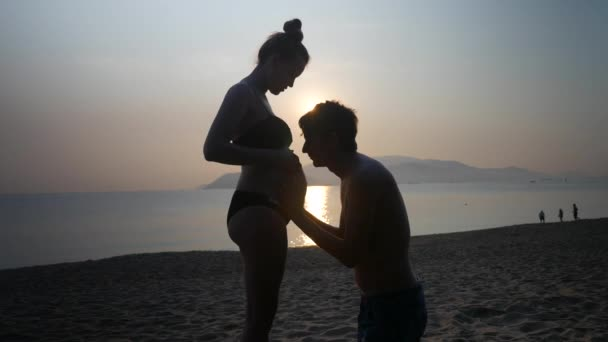 Silhouettes of pregnant in bikini and romantic man on bended knees caressing and kissing his wifes belly on a sea sunset background.
