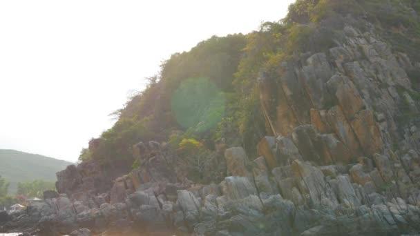 Skalnaté pobřeží s stromy v paprscích slunce. Panoramatický pohled z pohybující se lodi