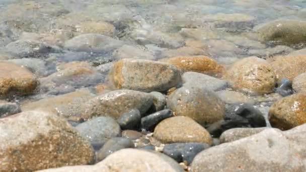 Kameny na břehu moře a vlny jasné mořské vody