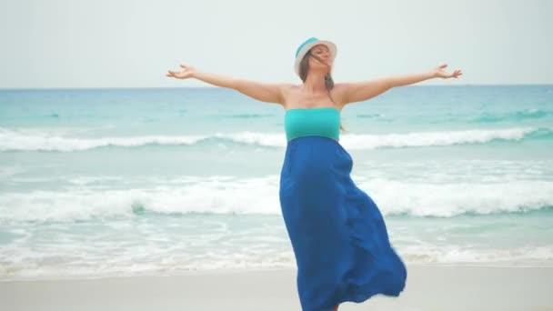 Krásná těhotná žena s zvedl ruce a vlající šaty na břehu Větrného moře