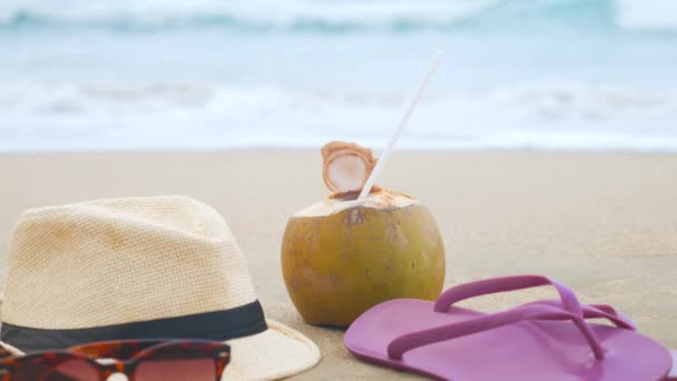 Coconut with drinking straw, hat, sunglasses and beach slippers on a sand at the sea