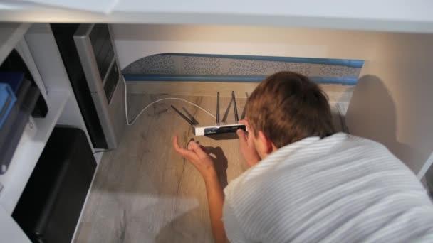 Mladý muž na podlaze se zařízením třást a klepání, snaží se pochopit, co je špatně