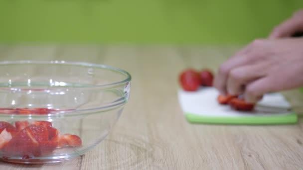 mužské ruce krájení čerstvé organické jahody - a položila ji na desku pro vaření jahody se smetanou, dolly jezdec výstřel, 2160p 4 k uhd