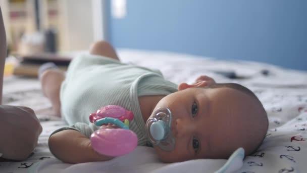 Novorozenec s růžovou hračkou sání dětské figuríny a při pohledu na fotoaparát attentivly
