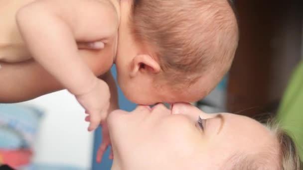 Chiuda in su di una giovane madre posa in aumento e che bacia il suo neonato dolce