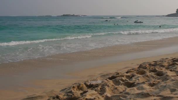Ocean seascape scenic of Unawatuna beach, Sri lanka with wave crashing on sandy shore.