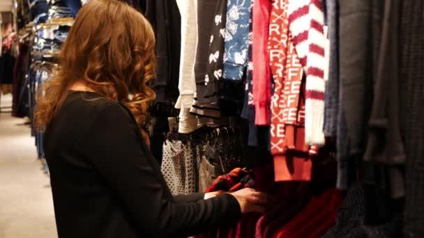Mladé krásné ženy, nákupy v módní mall, výběr nové oblečení, dívat se skrz závěsy s různé příležitostné barevných oděvů na ramínka