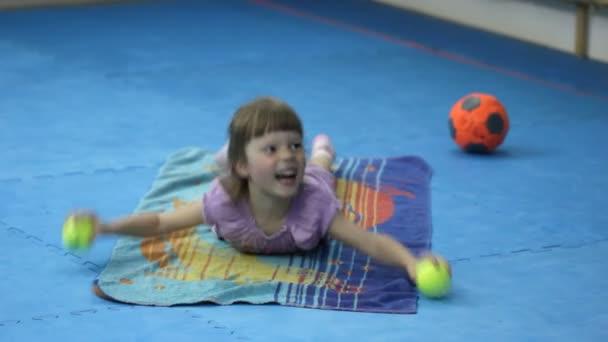Malá holčička se zabývá gymnastika s tenisové míčky