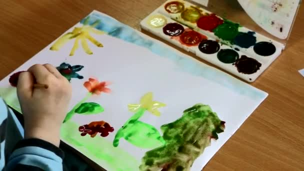 Childrens creativity. The child draws watercolors. He immersed in their fantasies. It is with enthusiasm and pleasure creates, invents