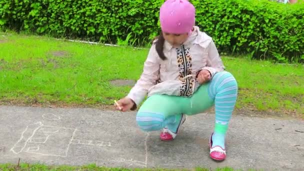 Childrens creativity. Girl draws with chalk on the pavement. She happily immersed in their fun. He fantasizes, invents, creates