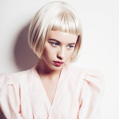 Portrait of a beautiful blond woman with short hair in the studio on a white background